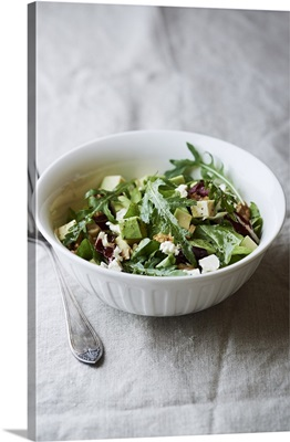 Bowl of freshly prepared leaf salad with avocado, walnuts and goat cheese