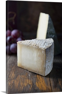 Hard cheese and grapes on a wooden surface