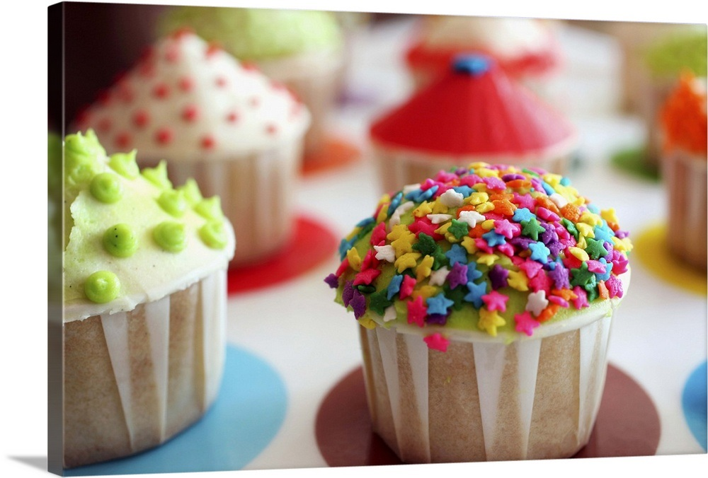 Multi-colored cupcakes on a tray, focus on cupcake with rainbow star  sprinkles