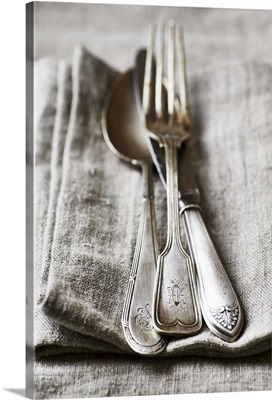Old silver cutlery on a linen cloth