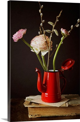 Ranunculus and pussy willow in red coffee pot on old book