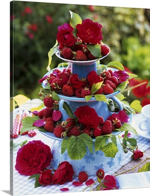 Raspberries and red roses on tiered stand of upturned cups