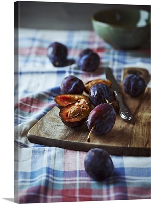Ripe plums on a wooden kitchen board
