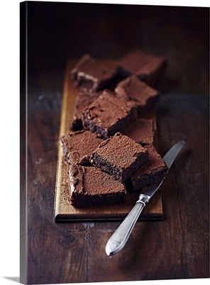Rustic chocolate brownies on a wooden board with a knife