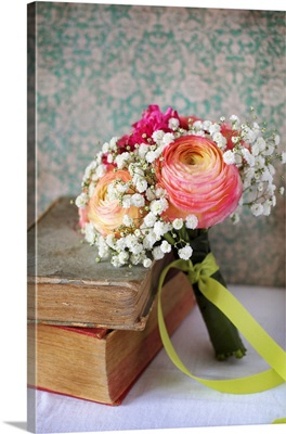 Spring posy with ranunculus and gypsophila next to old books