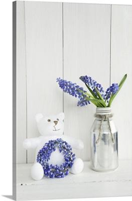 Teddy bear with wreath and posy of grape hyacinths