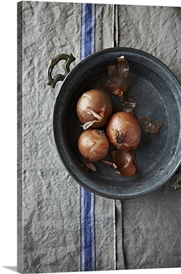 Three onions in a rustic bowl
