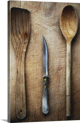 Two wooden spoons and a knife on a wooden chopping board