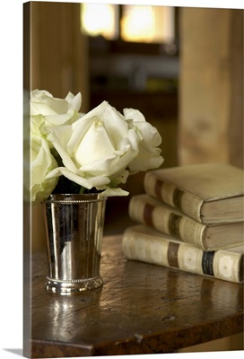 White roses in a silver cup and antique books on an old table top