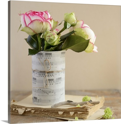 White roses in rolled up sheet music on an old book