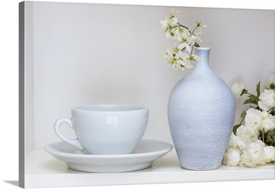 White still life with coffee cup and saucer, vase and cherry blossom