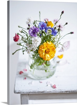 Wildflower bouquet in a water glass on a wooden table