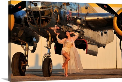 1940's pin-up girl in lingerie posing with a B-25 bomber