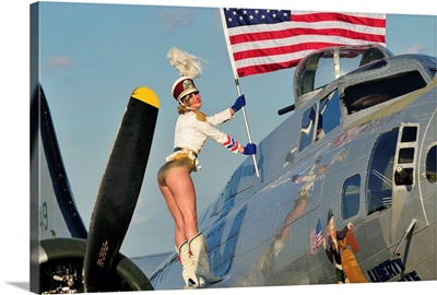1940's style majorette pin-up girl on a B-17 bomber with an American flag