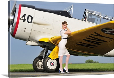1940's style Navy pin-up girl leaning on the wing of a T-6 Texan