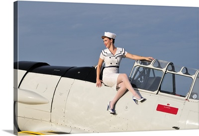 1940's style pin-up girl sitting outside the cockpit of a T-6 Texan