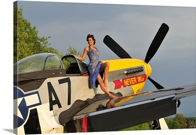 1940's style pin-up girl standing barefoot on the wing of a P-51 Mustang