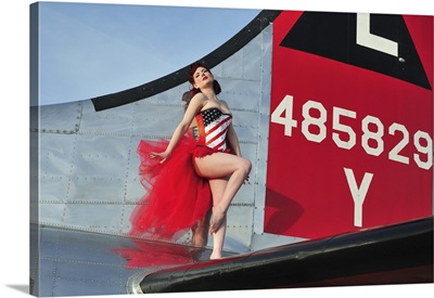 1940's style pin-up girl standing on the tail of a B-17 bomber