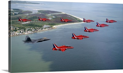 A F22 Raptor flies in formation with the Royal Air Force Aerobatic Team The Red Arrows