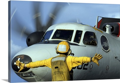 A flight deck director signals the pilot of an E-2C Hawkeye to spread his wings