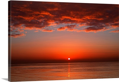 A layer of clouds is lit by the rising sun over Rio de la Plata, Buenos Aires, Argentina