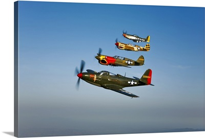 A P 36 Kingcobra, two Curtiss P 40N Warhawks, and a P 51D Mustang in flight