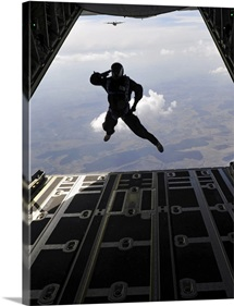 A paratrooper salutes as he jumps out of a C-130J Super Hercules