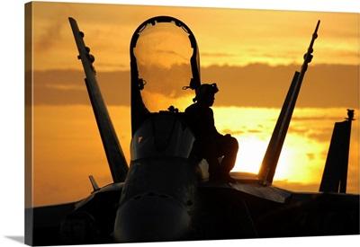 A plane captain enjoys a sunset from atop an F/A-18 Hornet
