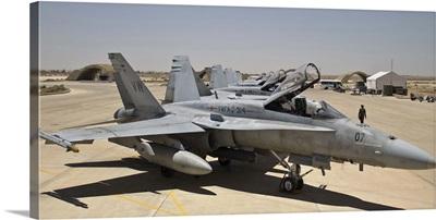 A row of U.S. Marine Corps F-18 Hornets await post-flight maintenance
