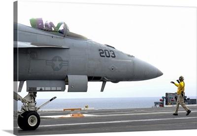 A Sailor directs an F/A-18 18E Super Hornet across the flight deck of USS Nimitz
