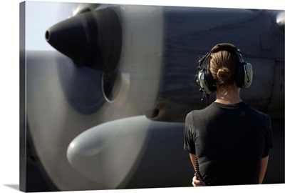 A soldier monitors the performance of a newly repaired C130 Hercules engine