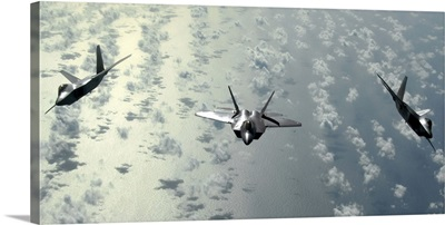 A three-ship formation of F-22 Raptors flies over the Pacific Ocean