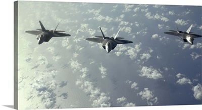 A threeship formation of F22 Raptors fly over the Pacific Ocean
