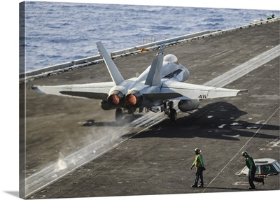 A U.S. Navy F/A-18C Hornet launches from the flight deck of USS Nimitz