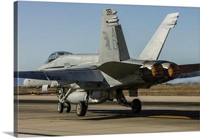A U.S. Navy F/A-18C Hornet lights the afterburners