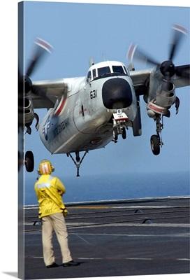 A US Navy officer observes a C2A Greyhound aircraft landing onboard USS Harry S Truman
