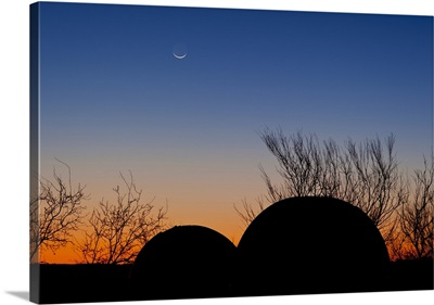 A young moon sets over two domed observatories, Crowell, Texas