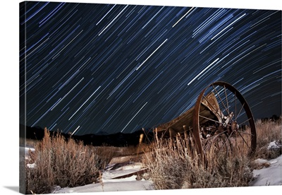 Abandoned farm equipment against a backdrop of star trails
