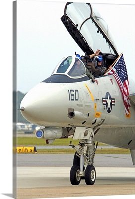 Air crewmen wave from their F14D Tomcat as they taxi