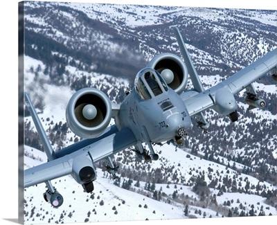 An A-10C Thunderbolt flies over the snowy Idaho countryside