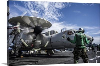 An aircraft director directs an E-2C Hawkeye aboard USS George Washington