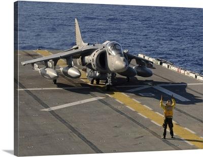 An Airman directs an AV 8B Harrier jet aircraft on the flight deck of USS Essex