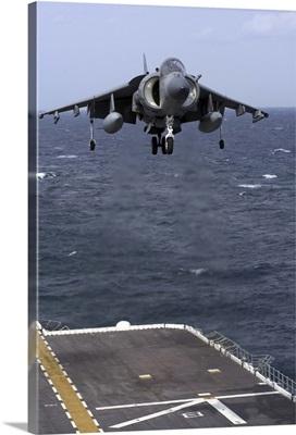 An AV-8B Harrier II prepares to land on the flight deck of USS Nassau