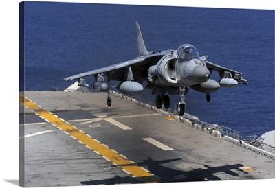 An AV-8B Harrier jet lands on the flight deck of USS Essex