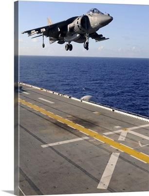 An AV-8B Harrier jet prepares to land on the flight deck of USS Essex