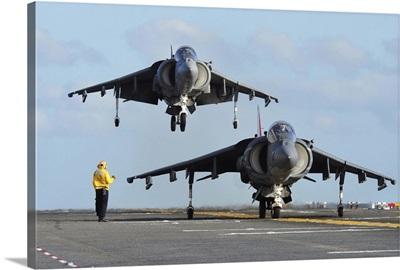 An AV-8B Harrier prepares for takeoff as another lands aboard USS Makin Island
