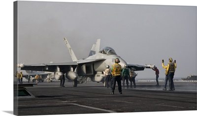 An EA-18G Growler is guided into catapult aboard USS George H.W. Bush