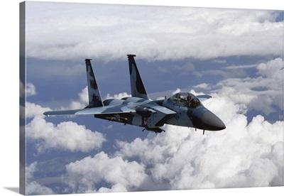 An F-15C Aggressor flies over a mountain range