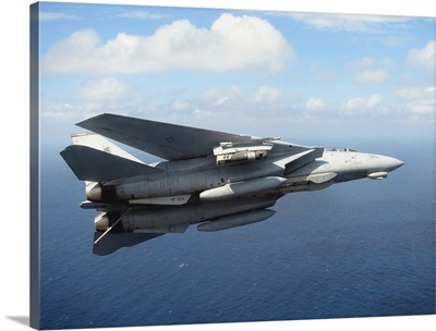 An F14D Tomcat banks with its tailhook lowered in preparation for landing