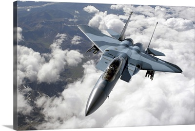 An F15C Aggressor flies over a mountain range